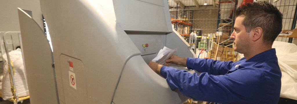 travailleur triant des déchets papiers dans une broyeuse géante