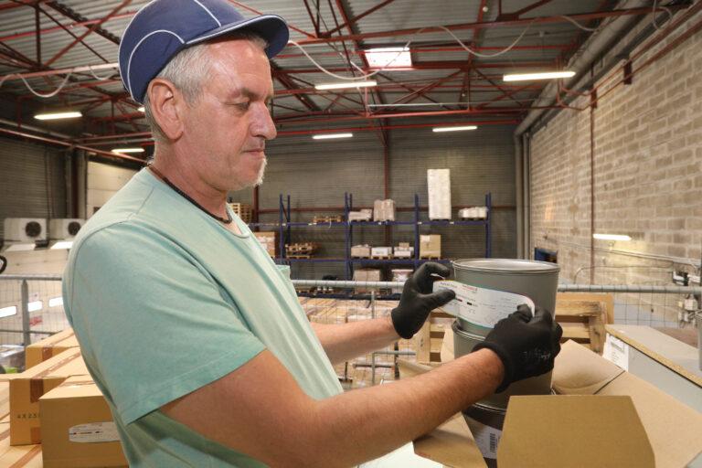 travailleur handicapé qui applique une étiquette sur un pot