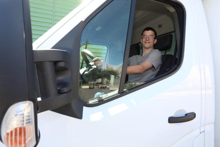 travailleur handicapé au volant d'un camion blanc