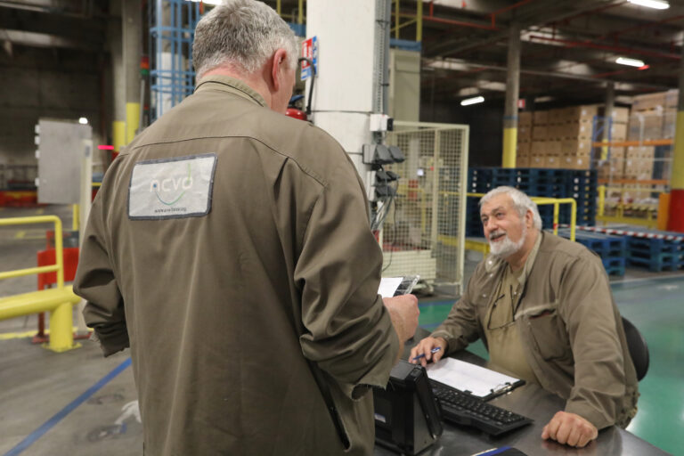 2 personnes en train de discuter dans un hangar