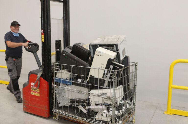 travailleur en situation de handicap qui pousse un chariot avec des ordinateurs